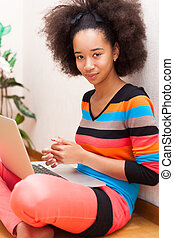 Black African American teenage girl with a afro haircut seated on the floor using a laptop computer
