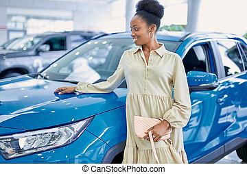 black african american woman posing next to blue car