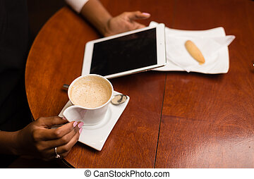 Black african american young yoman drinking coffee and using a tablet
