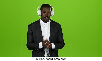 Black african guy listens to music through headphones and sings along. Green screen