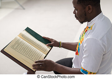 Black African Muslim Man Is Reading The Koran