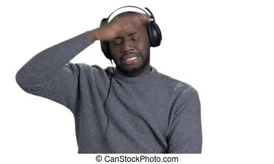 Black afro american man wearing headphones and dancing.