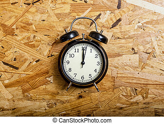 Black alarm clock in wood type Oriented Strand Board.