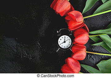 Black alarm clock near bouquet red tulips
