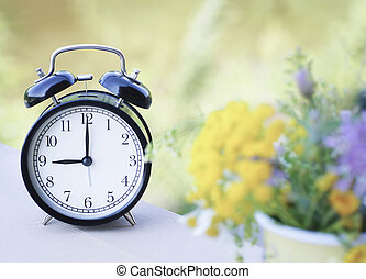black alarm clock on nature background with a blurred wildflowers