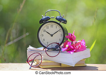Black alarm clock stacked on old dictionary with pink flower and glasses
