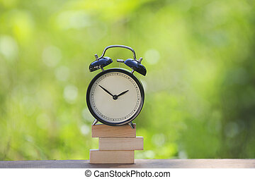 Black alarm clock stacked on wooden bar with shallow DOF green background. Business / Time Management concept.
