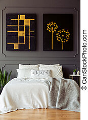 Black and gold posters above white bed with blanket in grey bedroom interior. Real photo