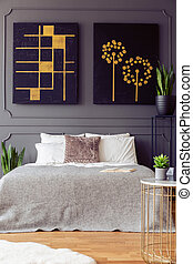 Black and gold posters on grey wall above bed with pillows in bedroom interior with plants. Real photo