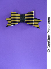 Black and golden striped bow tie over ultra violet background.