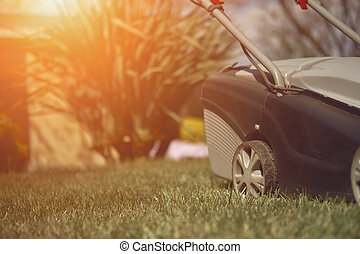 Black and gray modern grass-cutter mowing green lawn in a garden of country house. Gardening care equipment. Close up