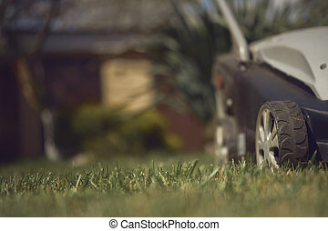 Black and gray professional lawn mower mowing green grass on backyard of country house. Gardening care equipment. Close up