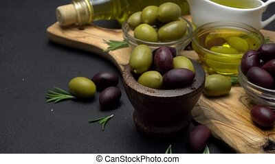 black and green olives and oil on wooden cutting board, dark...