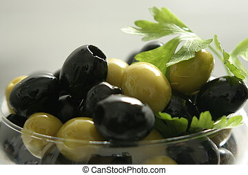 Black and green olives in a transparent vase with greens.