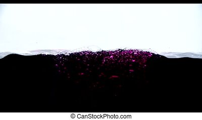Black and pink liquid with bubbles in slow motion on a white background
