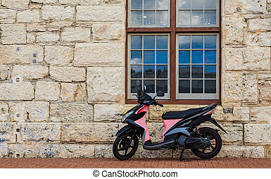 Black and Pink Scooter on Stone Wall Horizontal