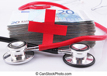Black and red stethoscopes with a wad of 20 Euro bills and Red Cross