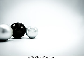 Black and silver Christmas baubles on white background.