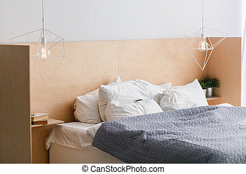 Black and white bed with wooden bedhead in loft interior, geometric lights