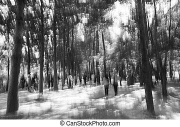 Black and white blurred image of people walking in the forest.