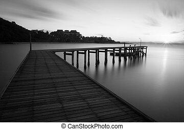 Black and white bridge over sea