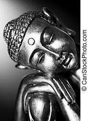 A black and white image of a Buddha statue resting, in front of a dark background.
