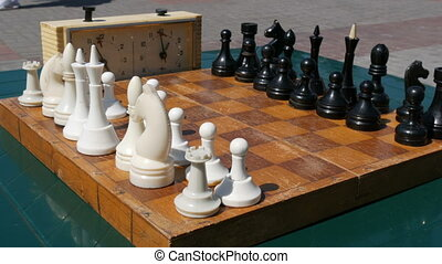 Black and white chess stand on the board, next to a vintage chess clock on the street