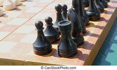 Black and white chess stand on the board, on the street