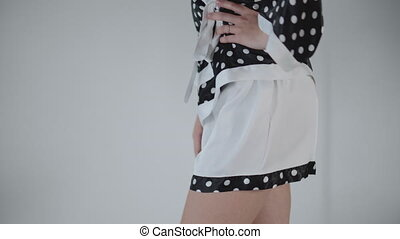 Black and white circle shorts shorts closeup. Happy girl dancing in front of the camera, posing in new pajamas on a white background.