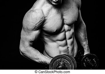 Black and white close-up of handsome power athletic mans hand stomach abs in training pumping up muscles with dumbbells