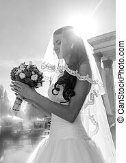 Black and white closeup portrait of cute bride looking at weddin