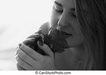 Black and white closeup portrait of young woman smelling rose