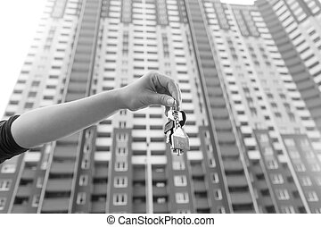 Black and white conceptual image of hand holding keys from new home against big building on background