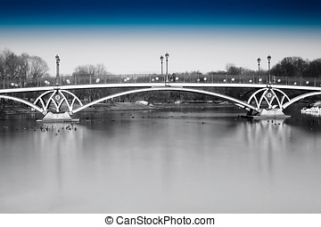 Black and white dramatic arc bridge in Moscow park with blue sky