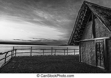 Black and white fishing hut at sunset