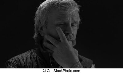 Black and white footage. Adult old man loses his beard looking at the camera in a dark room isolated on a black background. Prores 422