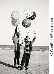 Black and white group portrait of two funny Caucasian children kids with bunch of balloons