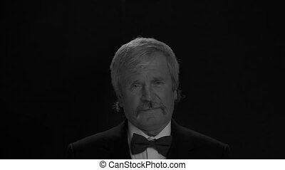 Black and white handsome old man in an tuxedo happily looks at the camera in a semi lit light room isolated on a black background. Prores 422