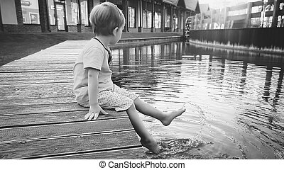 Black and white image of 3 years old toddler boy sitting on the pier at small river in town and holding feet in water