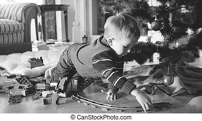 Black and white image of 4 years old little boy playing with toy railroad and train on floor at living room under Christmas tree