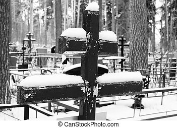 Black and white image of an old wooden cross covered with snow on the grave of an Orthodox cemetery in the winter.
