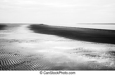 Black and white image of beach at low tide landscape