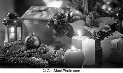 Black and white image of beautiful Christmas decorations and candles on wooden table