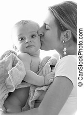 Black and white image of beautiful young mother kissing her baby boy covered in towel after bathing