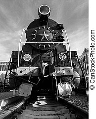 Black and white image of big black old steam train on the railroad