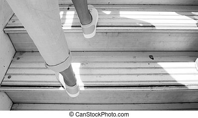 Black and white image of female feet on airplane doard stairs