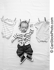 Black and white image of little baby boy in jeans hanging on cord next to drying clothes