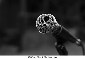 Black and white image of microphone with blured in background.