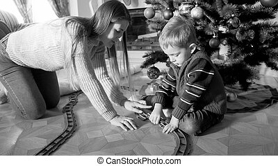 Black and white image of mother and little boy playing and building toy railroad at living room on Christmas morning. Child receiving presents and toy on New Year or Xmas