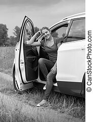 Black and white image of smiling young woman traveling by car opened door looking in camera